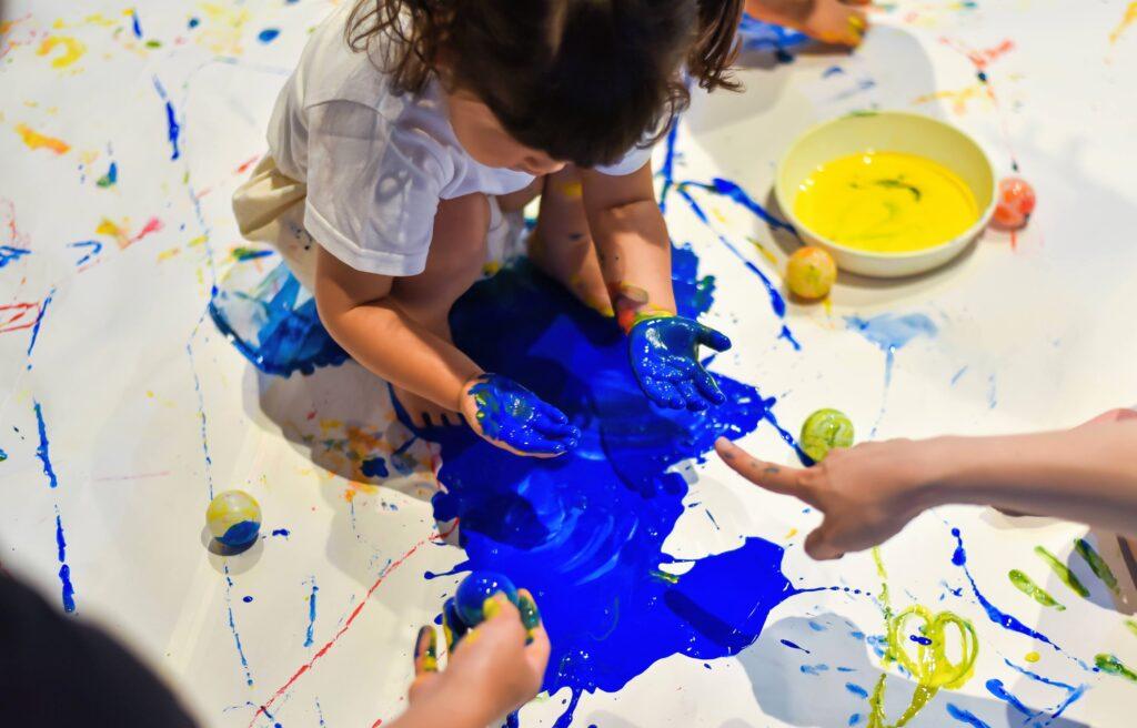 絵の具遊び。青い絵の具で遊ぶ女の子