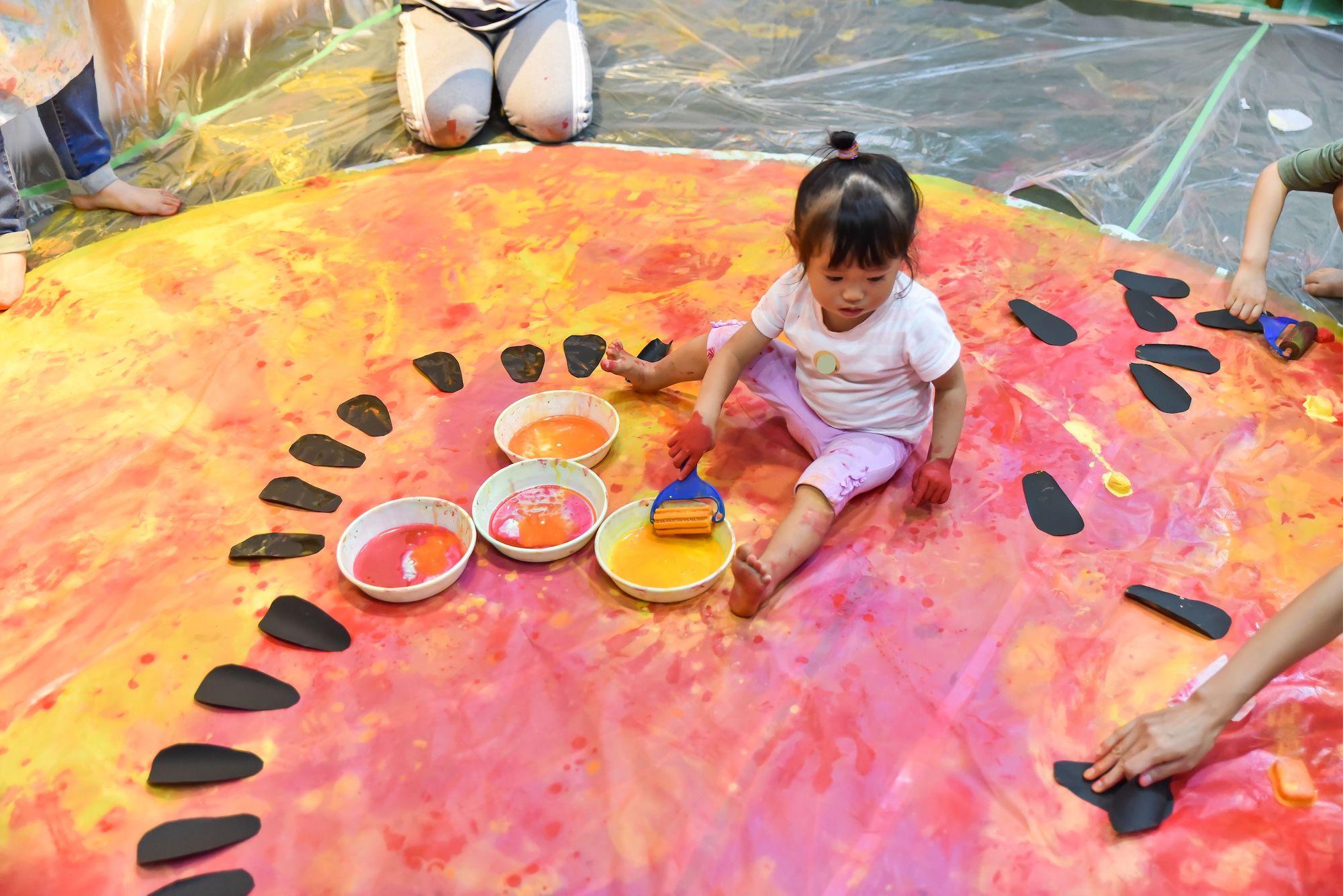 ぐちゃぐちゃ遊びで絵の具遊びを座って遊んでいる女の子